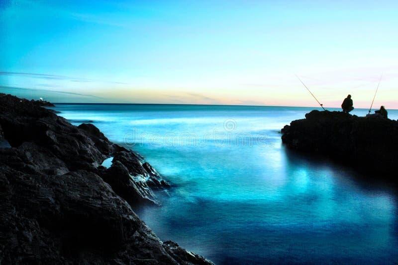 Het uur overzeese van de vredeszonsondergang magische blauwe visserijrotsen stock fotografie
