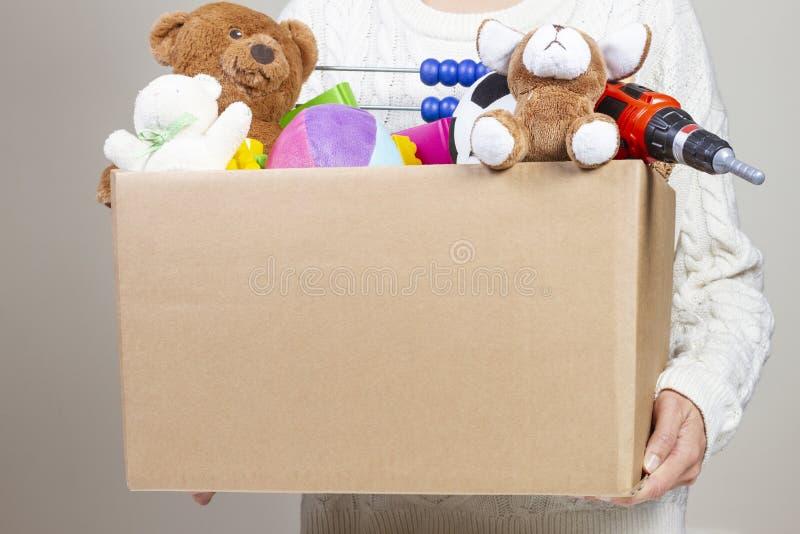 Het vakje van de de holdingsschenking van de vrouwenhand met kleren, speelgoed en boeken royalty-vrije stock foto's