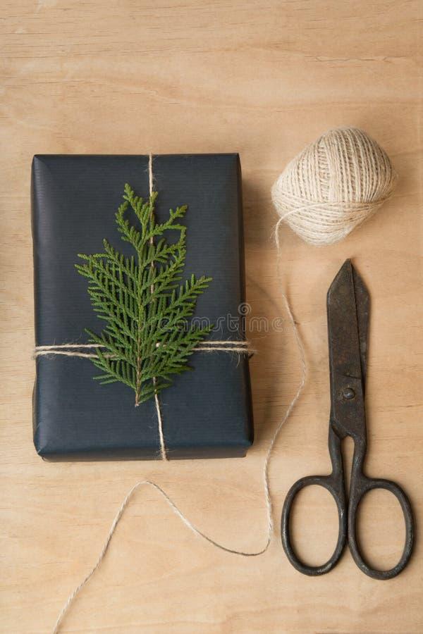 Het vakje van de Kerstmisgift dat in zwarte document en streng rond takcipres wordt verpakt op houten oppervlakte royalty-vrije stock afbeeldingen