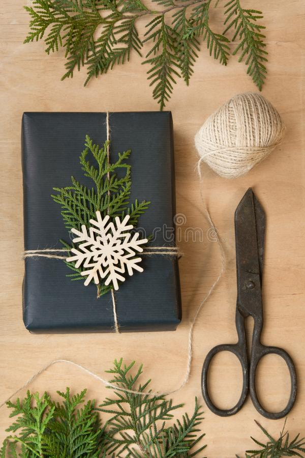 Het vakje van de Kerstmisgift dat in zwarte document en streng rond takcipres wordt verpakt op houten oppervlakte stock fotografie