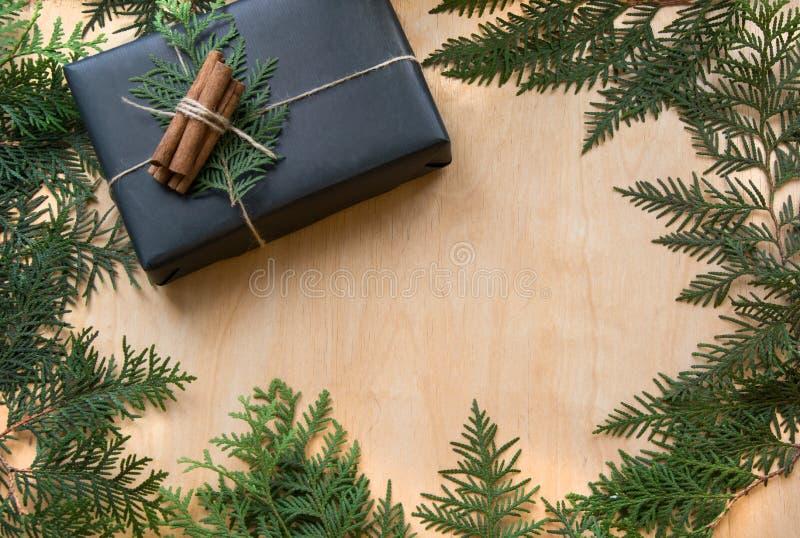 Het vakje van de Kerstmisgift in zwart document met decor rond takcipres wordt verpakt op houten oppervlakte die Rustieke stijl royalty-vrije stock afbeelding