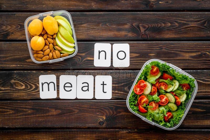 Het vakje van Togo met salade, noten, fruit en geen vleestekst voor vegetarische lunch op houten hoogste mening als achtergrond stock foto's