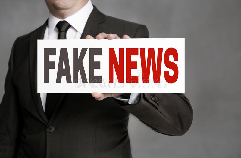 Het valse Nieuwsetiket wordt gehouden door zakenman stock foto's