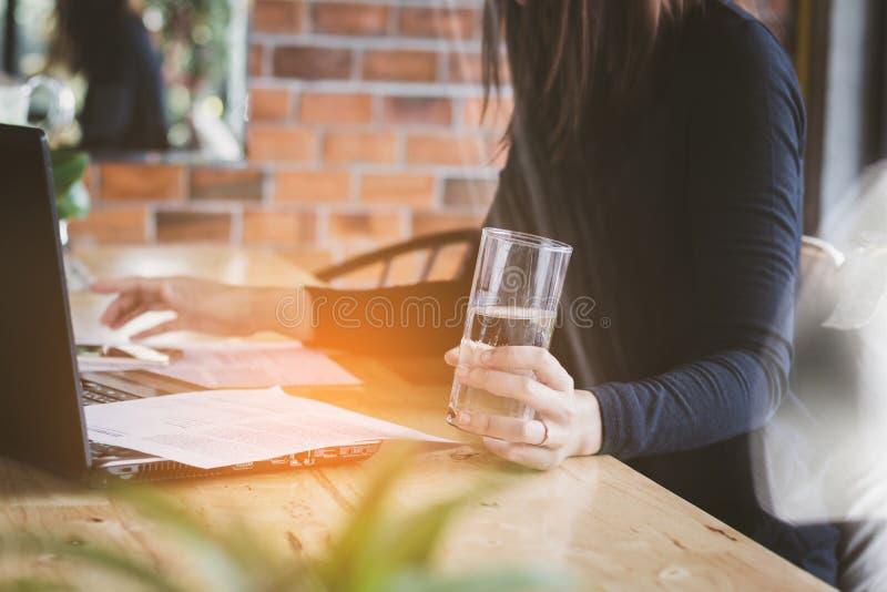 Het van bedrijfs Azië vrouw werken, drinkwater met ontspant, pret en gelukkig in bureau royalty-vrije stock afbeelding