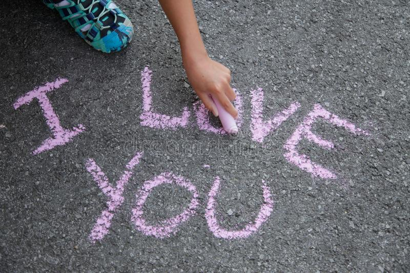 Het van letters voorzien I liefde u met roze krijt op grijs asfalt stock afbeelding