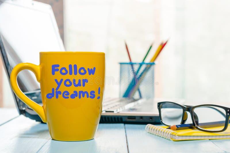 Het van letters voorzien van inspirational citaat volgt uw dromen op gele ochtendkoffie of andere hete drankkop thuis, zaken stock afbeeldingen