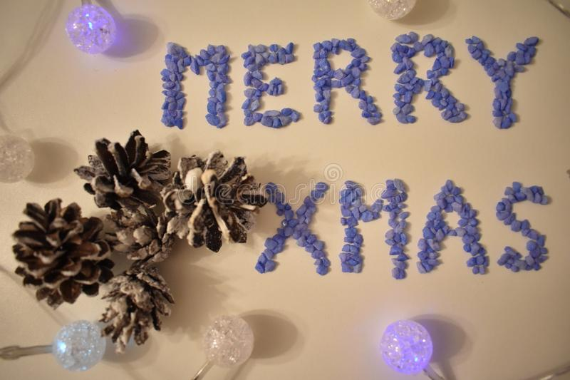 Het van letters voorzien Vrolijke Kerstmis van de Kleine Rotsen met Kegels en glanzende Ballen op de witte achtergrond stock afbeelding