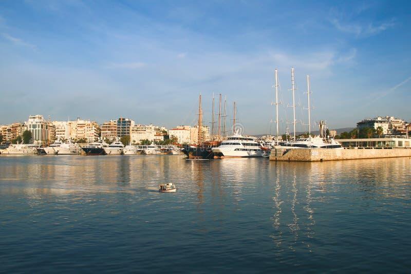 Het varen, motorboten en een kleine vissersboot die kalme wateren in de haven van jachthaven Zeas kruisen Pireas Griekenland stock foto's