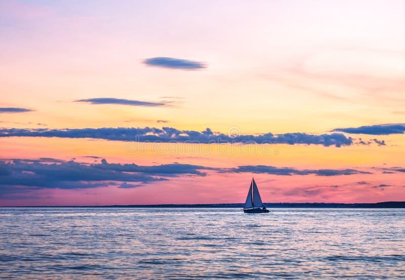 Het varen onder de het plaatsen zon Luchtwolken van verschillende kleuren stock afbeelding