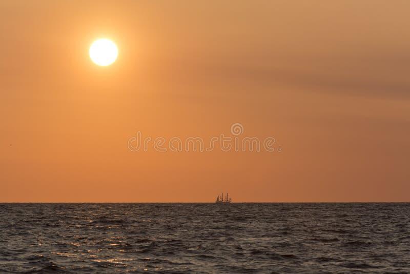 Het varen tallship op horizon en grote zon stock afbeelding