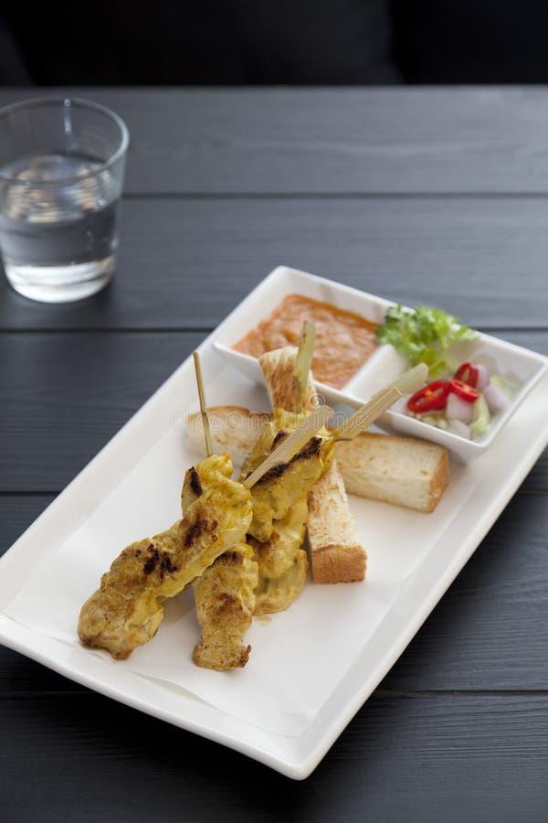 Het varkensvlees Satay, Geroosterde varkensvleesstok op witte plaat diende met zoete pinda onderdompelende saus en azijn stock foto