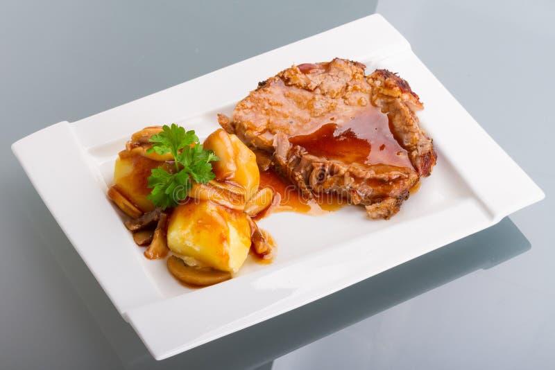 Het varkensvlees van het braadstuk met jus en aardappels royalty-vrije stock afbeelding