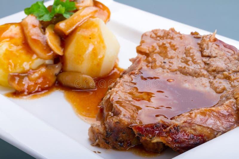 Het varkensvlees van het braadstuk met jus en aardappels stock fotografie