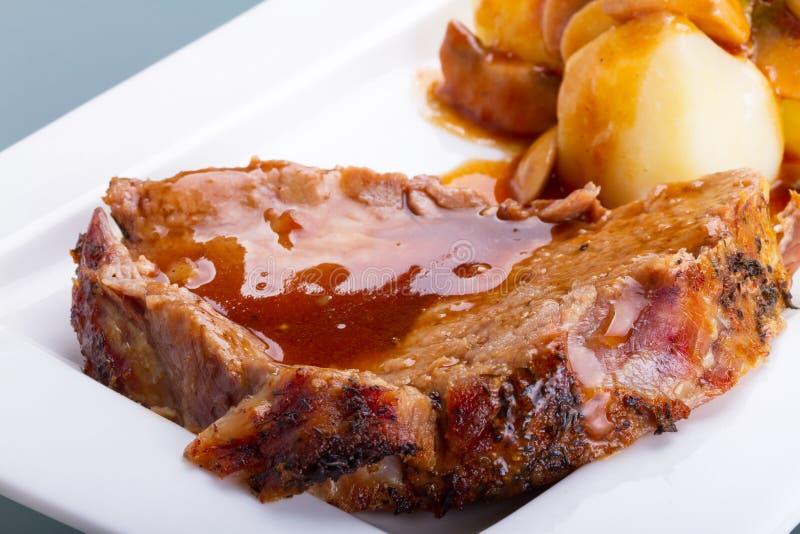 Het varkensvlees van het braadstuk met jus en aardappels stock foto's