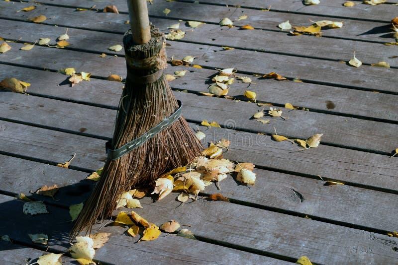 Het vegen van een houten terras met een bezem en het verwijderen van de herfstbladeren royalty-vrije stock afbeeldingen