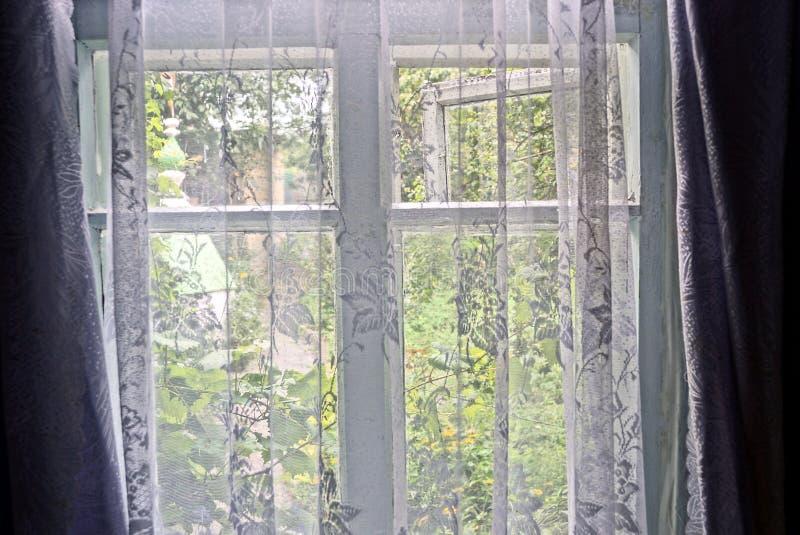 Het venster in de ruimte is behandeld met een transparant gordijn stock fotografie
