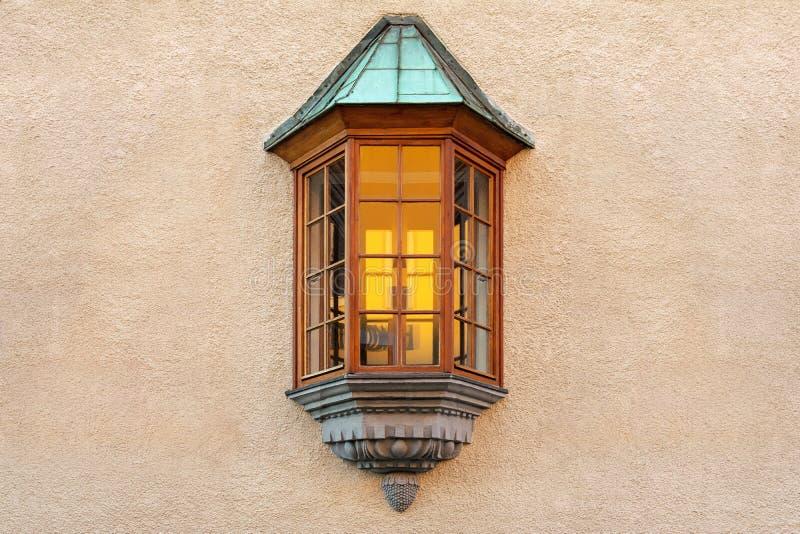 Het venster in de vorm van een erker wordt gevestigd in het midden van de gepleisterde muur van het gebouw stock foto