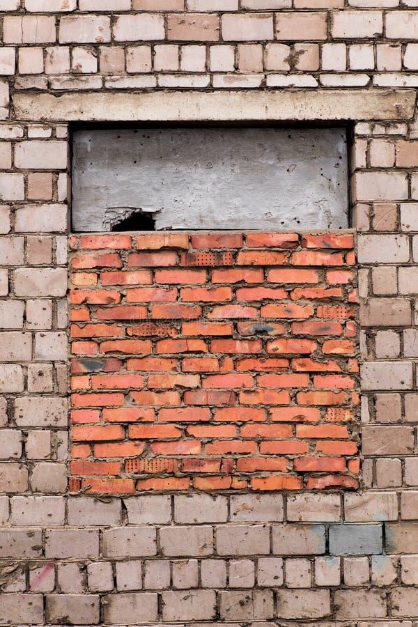 Het venster is omhoog bricked Het venster is gelegde baksteen Grijze bakstenen muur met een venster dat met rode baksteen wordt g stock fotografie