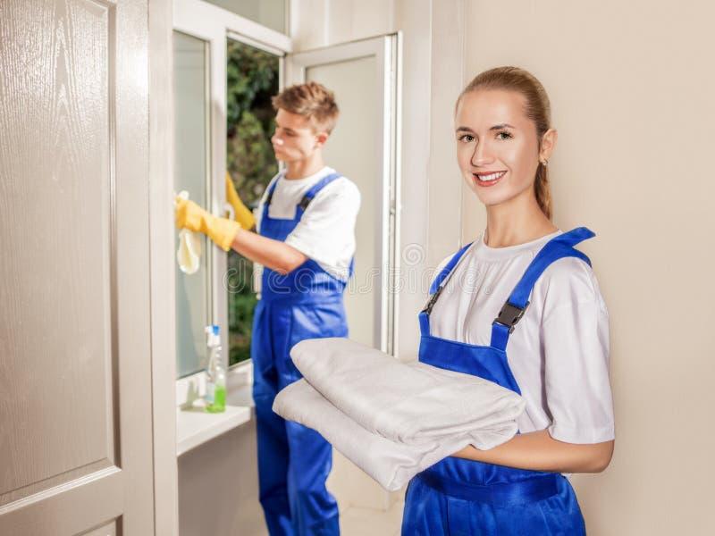 Het venster schoonmaken en dienst die binnenshuis de glimlachen stock fotografie