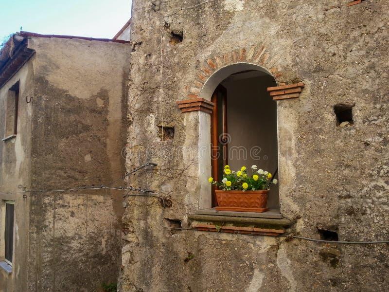 In het venster van de oude grijze baksteen bouw is er een bruine pot met heldere gele bloemen en groen gebladerte, Maratea stock foto's