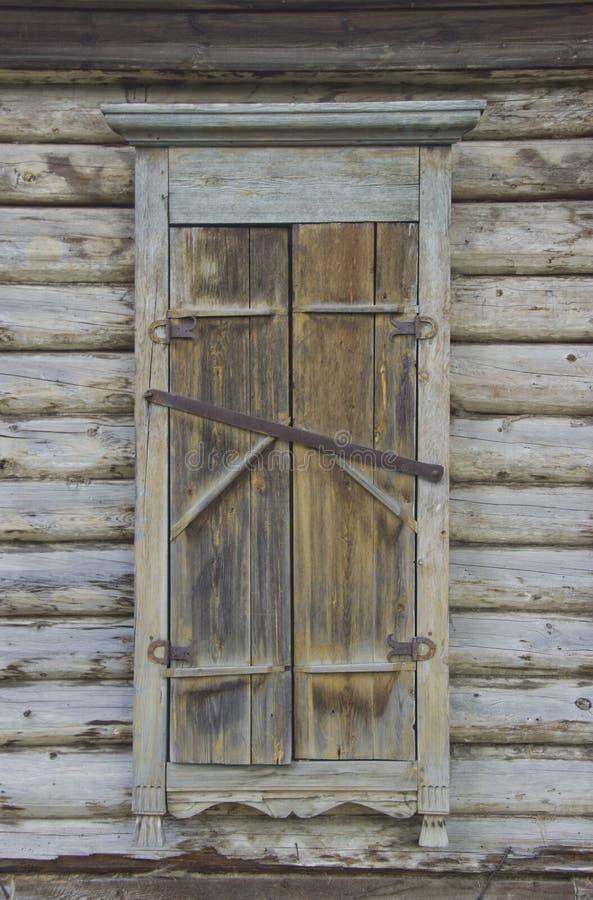 Het venster van een oud die blokhuis, met blinden wordt gesloten stock foto's