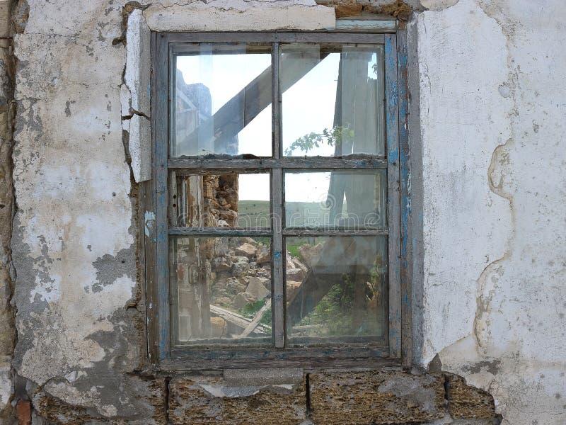 Het venster van een verlaten en vernietigd huis, waarin vele jaren niemand leeft stock foto's