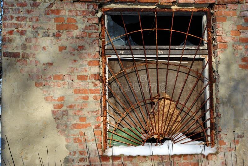 Het venster van het oude die baksteengebouw met roestige ijzerrooster wordt behandeld, sneeuw op venstervensterbank stock foto's