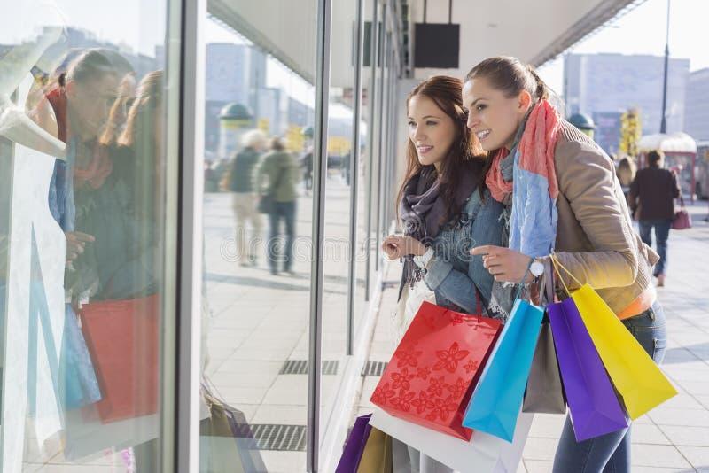 Het venster van Shopaholic het vrouwelijke vrienden winkelen stock foto