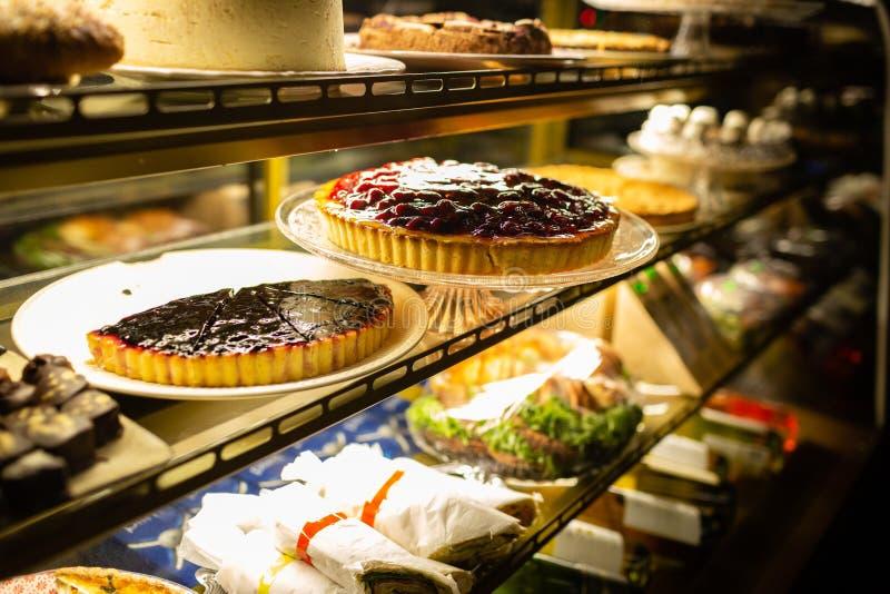 Het vensterhoogtepunt van de koffiewinkel van zoete cakes en andere banketbakkerij stock afbeelding