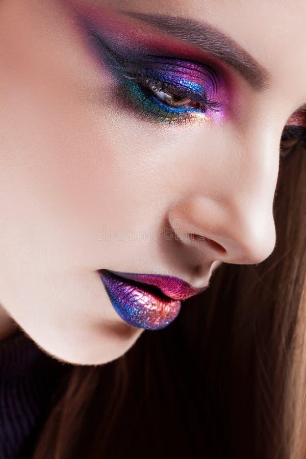 Het verbazen Heldere oogmake-up in luxueuze blauwe schaduwen De mooie jonge vrouw met heldere make-up, kijkt neer stock afbeeldingen