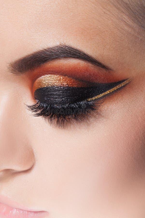 Het verbazen Heldere oogmake-up met een brede pijl Bruine en gouden tonen, gekleurde oogschaduw stock fotografie