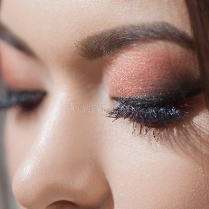 Het verbazen Heldere oogmake-up met een brede pijl Bruine en rode tonen, gekleurde oogschaduw royalty-vrije stock afbeelding