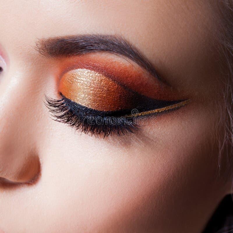 Het verbazen Heldere oogmake-up met een spectaculaire pijl Bruine en gouden tonen, gekleurde oogschaduw stock foto