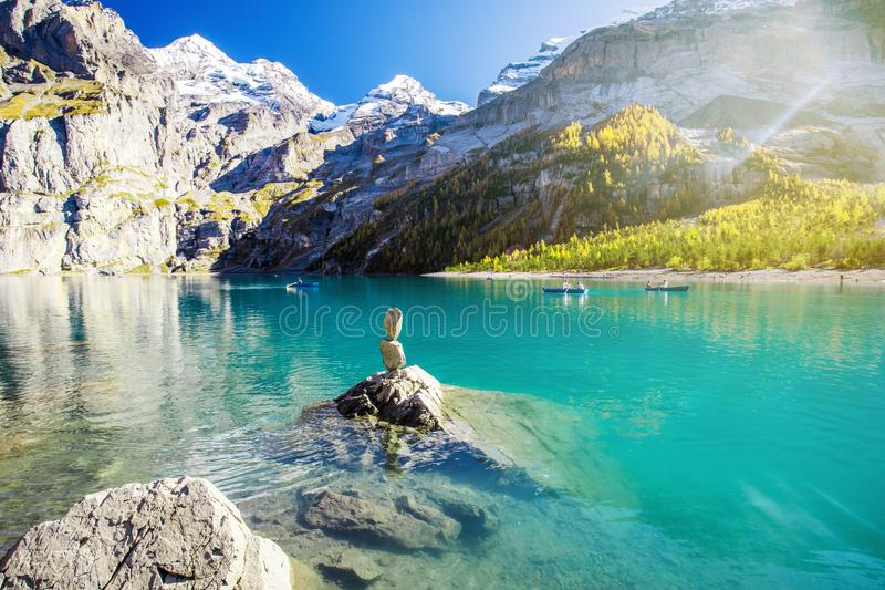 Het verbazen tourquise Oeschinnensee met watervallen, houten chalet en Zwitserse Alpen, Berner Oberland, Zwitserland stock afbeelding