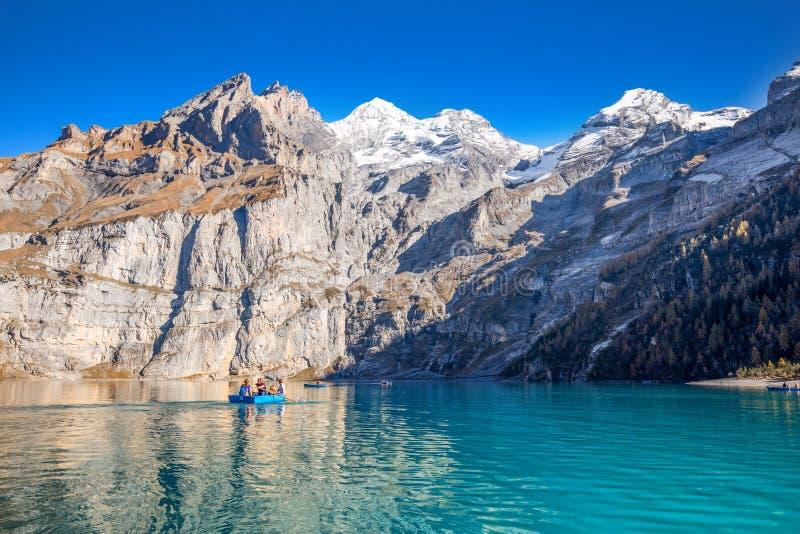 Het verbazen tourquise Oeschinnensee met watervallen, houten chalet en Zwitserse Alpen, Berner Oberland, Zwitserland royalty-vrije stock foto's