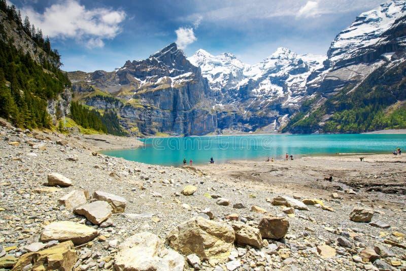 Het verbazen tourquise Oeschinnensee met watervallen, houten chalet en Zwitserse Alpen, Berner Oberland, Zwitserland stock foto's