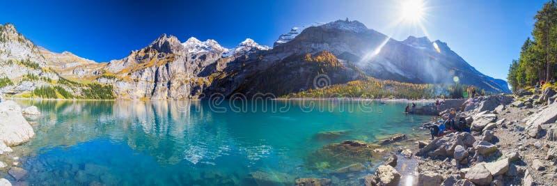 Het verbazen tourquise Oeschinnensee met watervallen, houten chalet en Zwitserse Alpen, Berner Oberland, Zwitserland stock fotografie