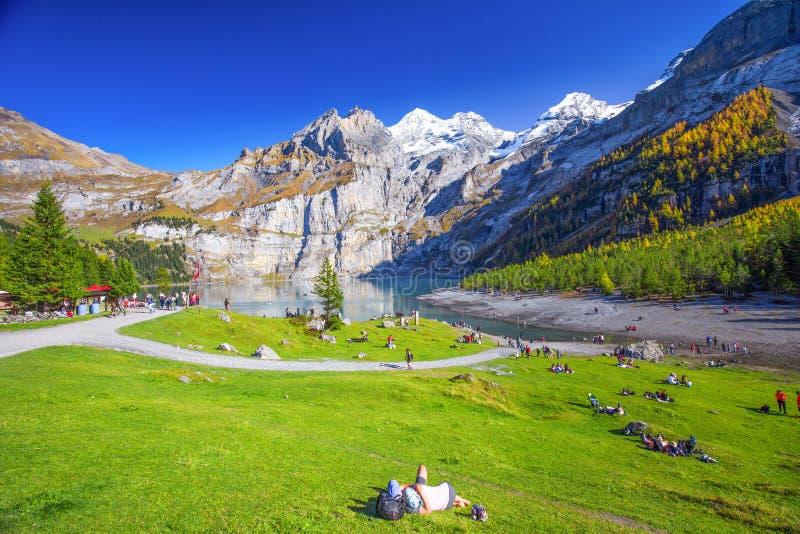 Het verbazen tourquise Oeschinnensee met watervallen, houten chalet en Zwitserse Alpen, Berner Oberland, Zwitserland royalty-vrije stock fotografie