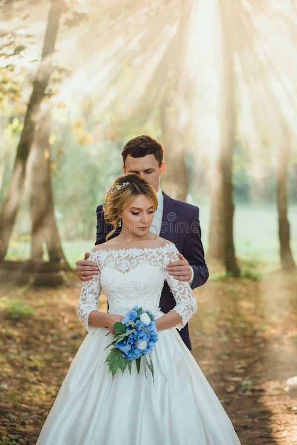 Het verbazen van aantrekkelijk jong paar in huwelijksdag bruid in elegante witte lange kleding en blauw boeket ter beschikking, b stock fotografie
