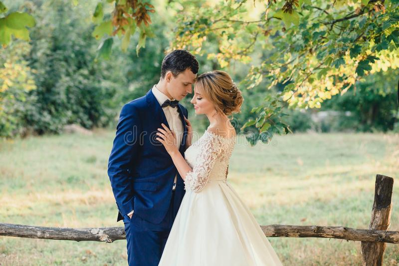 Het verbazen van aantrekkelijk jong paar met gesloten ogen in huwelijksdag bruid in elegante witte lange kleding en blauw boeket  royalty-vrije stock foto's