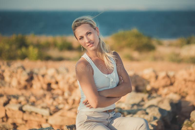 Het verbazen van dame blonde vrouw in het lichte witte modieuze kleren sexy stellen op overzeese zijstrandlucht Sterretjemeisje d royalty-vrije stock foto