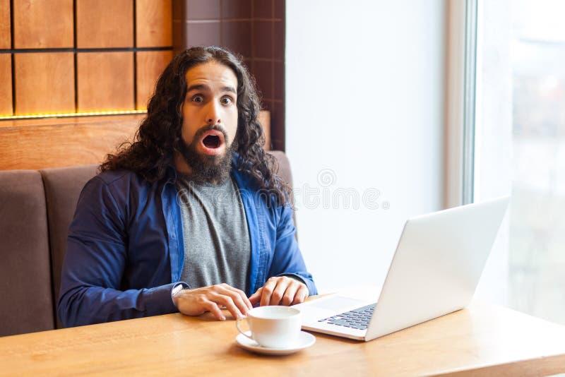 Het verbazen van de knappe jonge volwassen mens freelancer in toevallige stijlzitting in koffie met laptop en het bekijken camera stock fotografie
