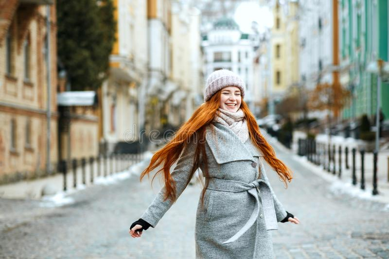 Het verbazen van glimlachend roodharigemeisje die modieuze walki van de de winteruitrusting dragen royalty-vrije stock afbeeldingen