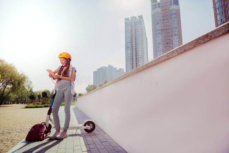 Het verbazen van longhaired meisje die haar gadget in handen houden stock fotografie