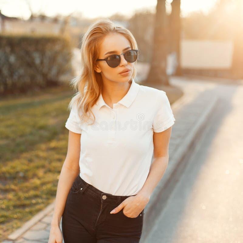 Het verbazen van modieuze jonge hipstervrouw in modieuze de zomerkleren bevindt zich en stelt bij zonsondergang van de zomer Aant stock foto