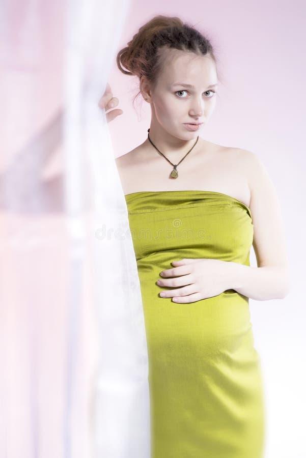 Het verbazen van schoonheids zwangere vrouw achter gordijn stock foto's