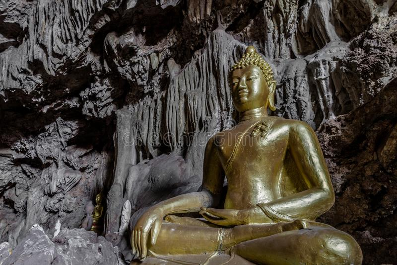 Het verbazende gouden standbeeld van Boedha in mooi hol, heilig natuurlijk boeddhistisch heiligdom in Thailand stock afbeelding