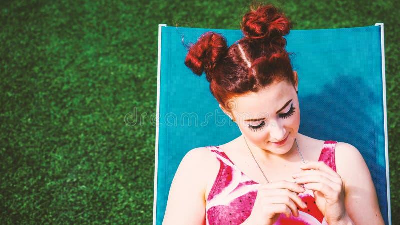 Het verbazende jonge roodharige stellen op gras royalty-vrije stock afbeeldingen
