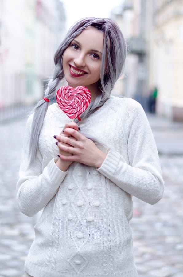 Het verbazende meisje van het close-upportret in de witte warme wollen sweater met grijs zilveren haar met rode en witte lolly royalty-vrije stock afbeelding