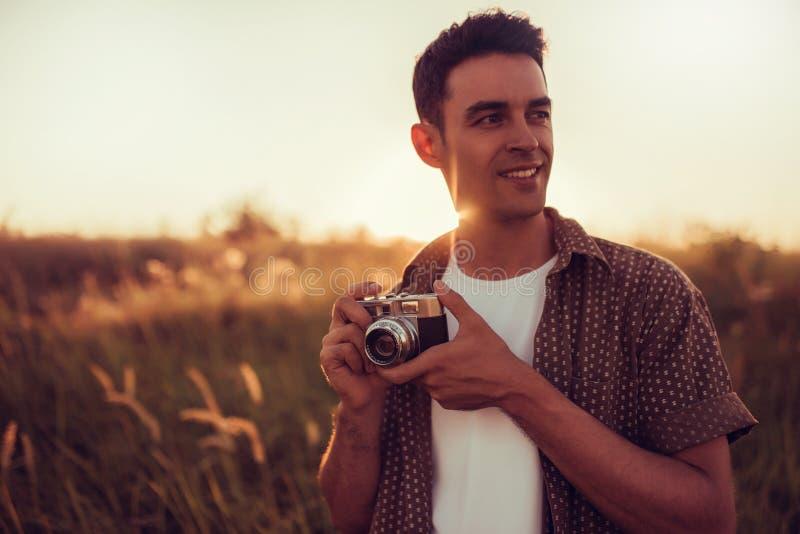 Het verbazende portret van de jonge knappe mens met uitstekende camera kijkt naar één kant, op gebiedsachtergrond, en op zonsonde royalty-vrije stock fotografie